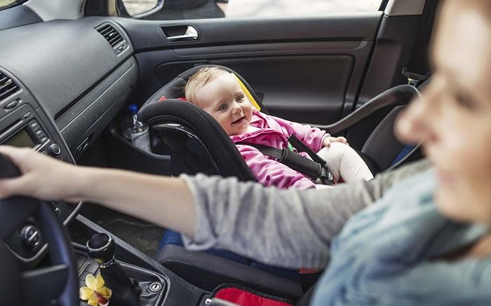 Mother driving a car, having her little baby girl in a child seat