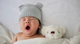 bébé avec peluche au lit